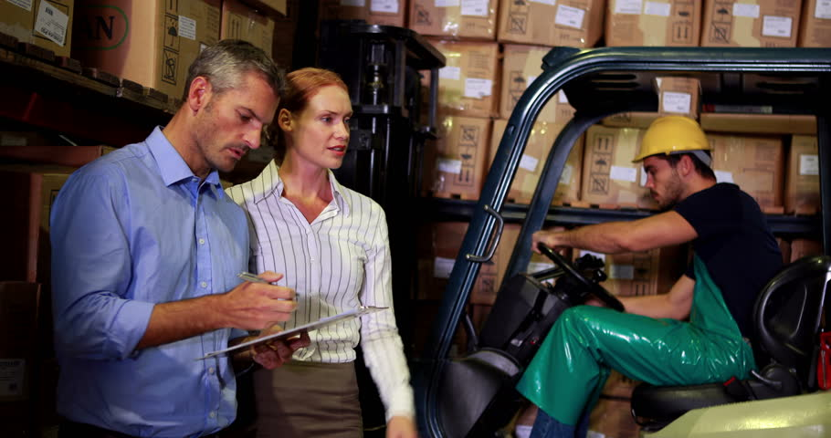 Warehouse management talking with forklift driver behind in a large warehouse | Shutterstock HD Video #6857509