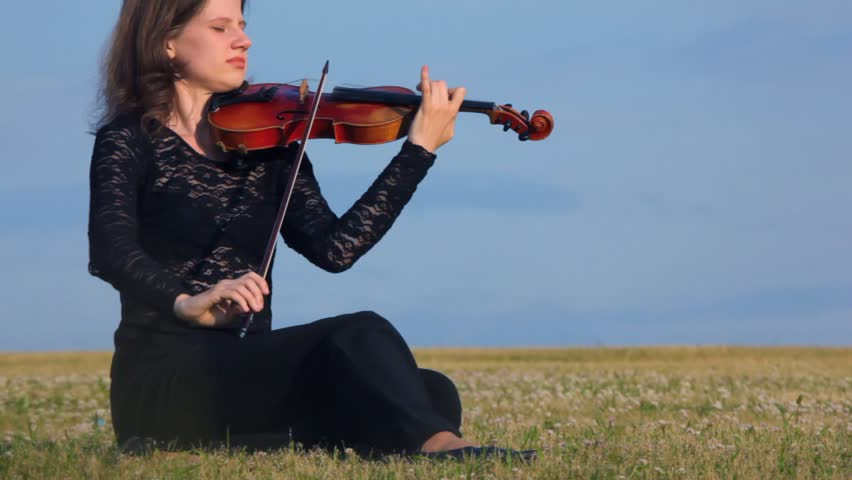 young female musician plays violin sits in autumn field with yellow grass
