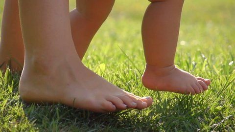 Little baby learns to walk. Mother is teaching her child to do the first steps on a green grass in summer. Close up on feet. Slow motion filmed at 250 fps.