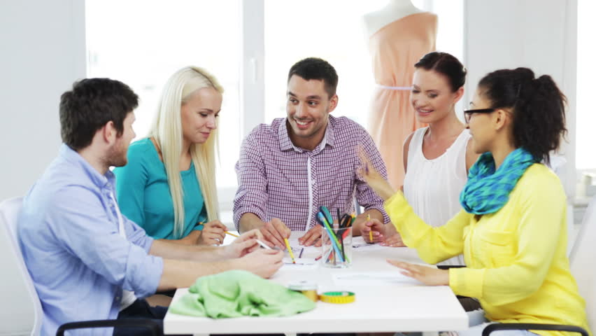Startup, fashion, teamwork and office concept - smiling fashion designers working in office | Shutterstock HD Video #6982018