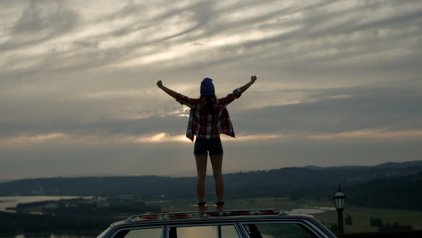 Young Woman Stands On Her Car And Takes In The Surrounding Beauty, She Raises Her Arms And Jumps Up And Down In Awe Of The View