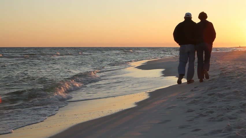 Mature loving couple walk away on the beach at dusk in the winter. They are bundled up for the cold wind.