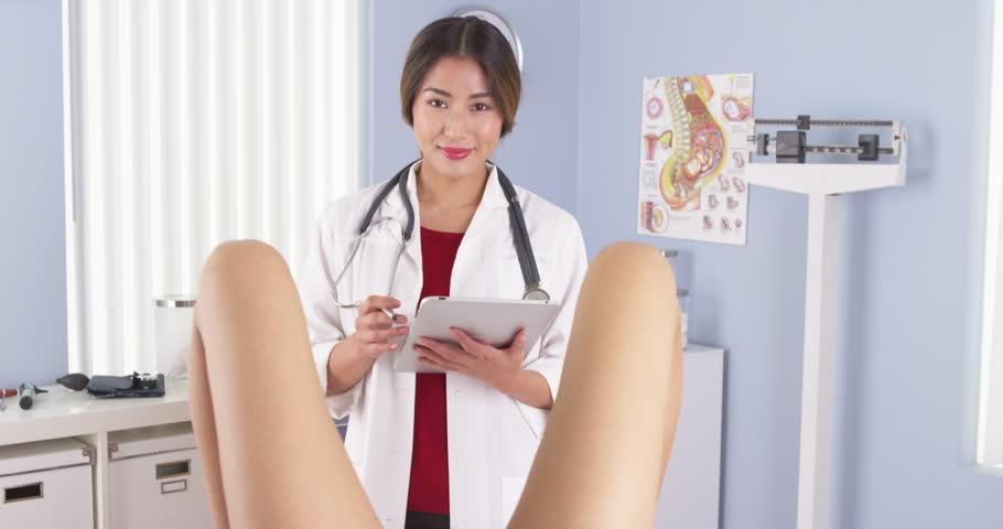 Asian OBGYN examining patient in hospital exam room