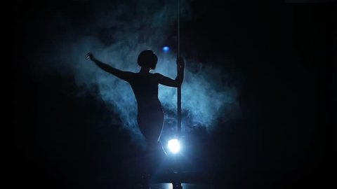 Silhouette of a sexy female pole dancing on blue background