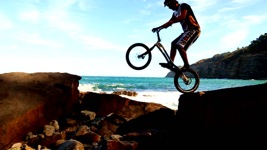 A man jumps from one rock to another with his trials BMX near the beach #7032469