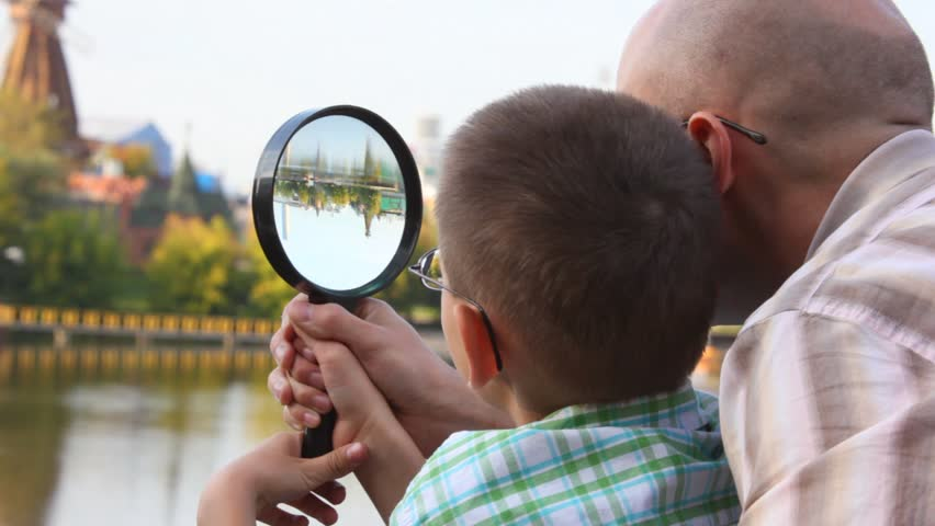 father and son standing on bank of river and looks through magnifying glass