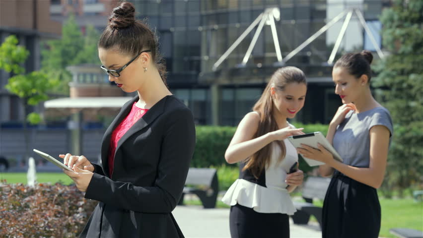 Confident three successful business woman at the business centre out of the office, smiling directly at the camera.Business woman working on a tablet on the background of their business partners. | Shutterstock HD Video #7110139