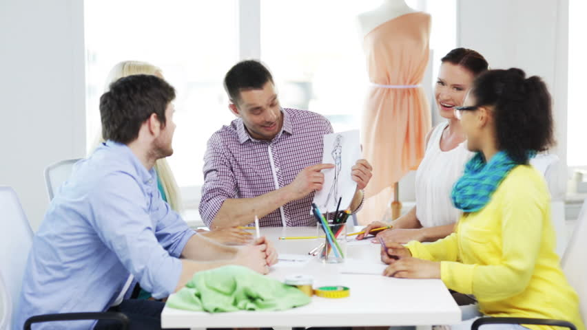 Startup, fashion, teamwork and office concept - smiling fashion designers working in office | Shutterstock HD Video #7133488