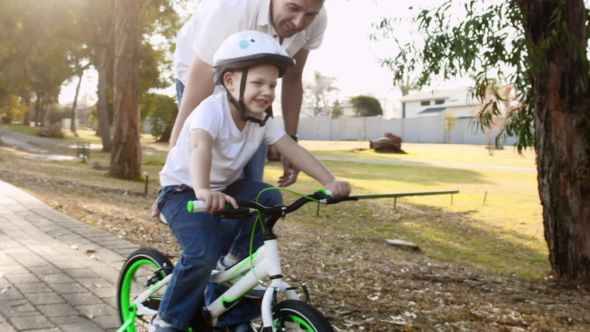 Steadicam shot of father teaching son how to ride his bike on a park pathway with safety helmet.