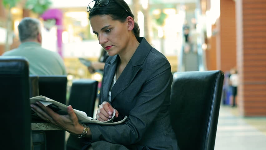 Businesswoman reading newspaper in restaurant in modern place