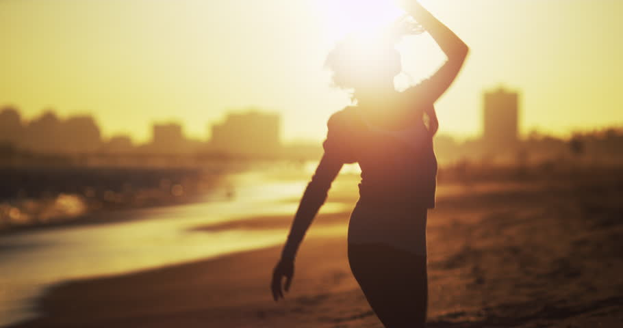 Black woman dancing at the beach at sunset