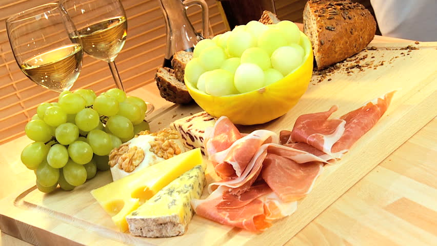Healthy selection of cheese, oils, fruit & parma ham served with white wine as a modern lifestyle lunch