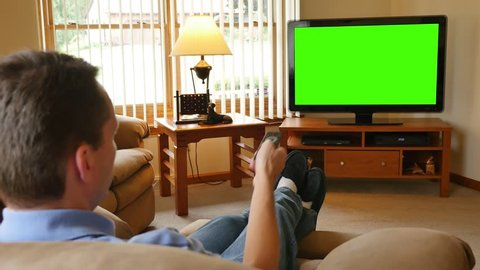A man in his living room changes the channel and watches television. Green screen for your custom content.
