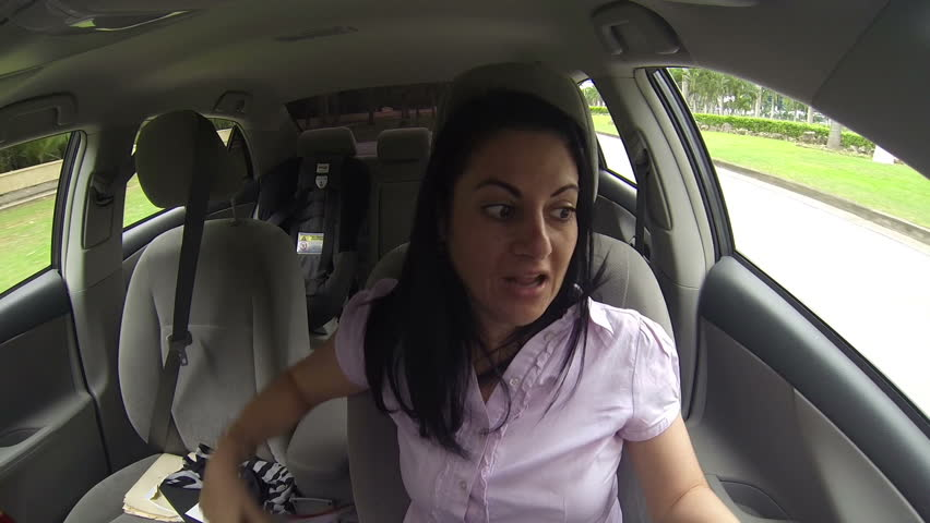 Woman looking for clothes in the car while driving. | Shutterstock HD Video #7239889