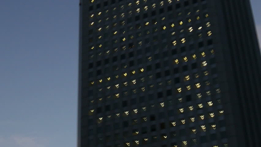 Zoom out shot from a Skyscraper in Shinjuku lighting up in sunset skies. | Shutterstock HD Video #7263772