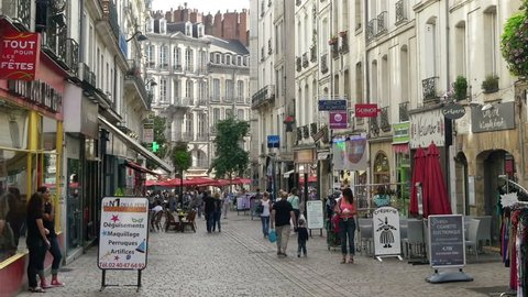 NANTES FRANCE - AUGUST 2014: Looking along the pedestrian shopping street called Rue de Verdun in the city of Nantes. This typical people only street is lined with small shops, cafes and restaurants.