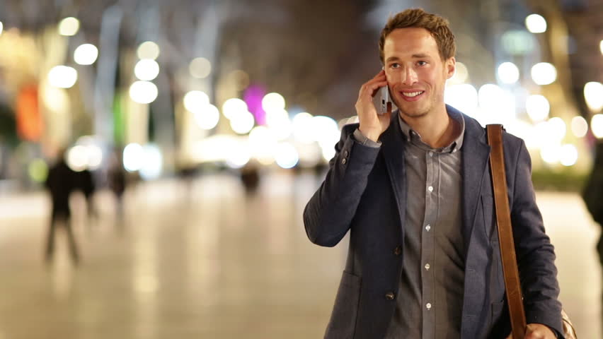 Smartphone man talking on smart phone at night on walking street. Handsome young casual business man talking on mobile cell phone smiling happy wearing suit jacket outdoors. | Shutterstock HD Video #7359769