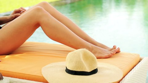 Female feet on sunbed by the swimming pool
