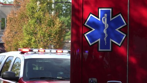 ARLINGTON, VIRGINA - SEPT. 2014: Star of Life on side of fire department EMS vehicle under mottled light; lights flashing bg. Star of Life is used to identify medical personnel, equipment & vehicles