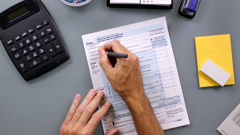 Time-lapse of man filling out a United State 1040EZ income tax form. Names and info are ficticious.