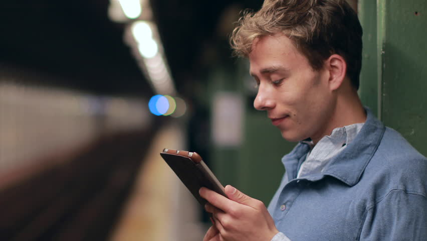 Young caucasian man using tablet pc on subway platform | Shutterstock HD Video #7451569