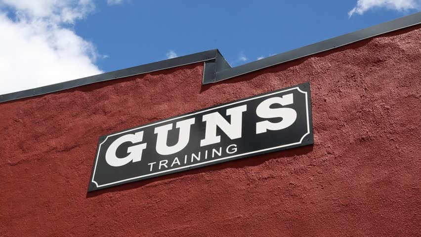 Deadwood, South Dakota, July 2014: The camera tilts down from a shop sign stating gun training to the front door of Deadwood Jakes Guns and Ammo in Deadwood, South Dakota, July 2014.