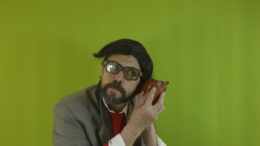 An untidy bizarre man, wearing big patched glasses and a toupee, trying to tune in a station on an old transistor radio, over green background