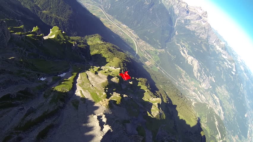 A base jumper in a wingsuit gliding down over a green landscape, POV