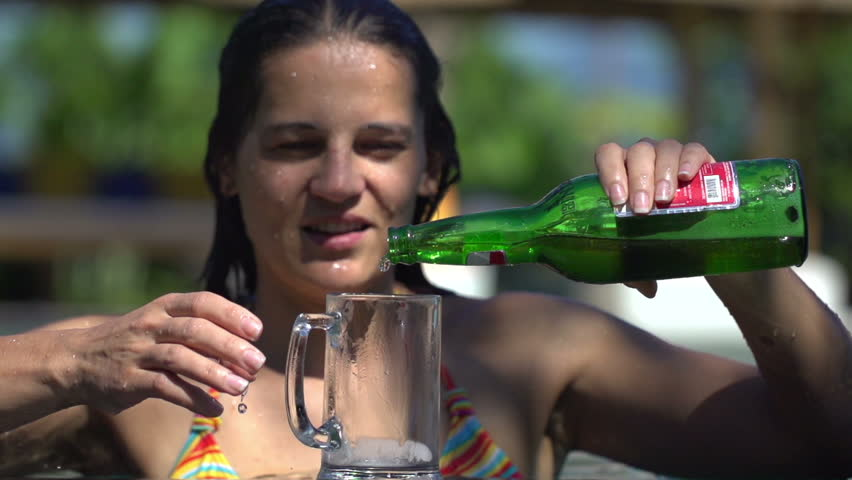 Woman in pool pouring beer into glass, super slow motion, 240fps  | Shutterstock HD Video #7496389