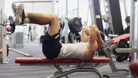 sport, bodybuilding, lifestyle and people concept - young man making abdominal exercises in gym