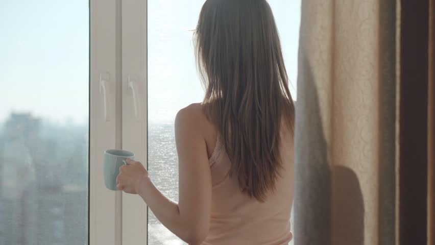 Young woman drinking coffee by the window during sunrise in her cozy home. Relaxed morning at home concept. Slow motion filmed at 250 fps.