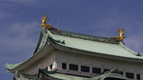 Kinshachi, or golden dolphins (called that, although they do not look like dolphins) on top of the main tower of Nagoya Castle in Nagoya City, Aichi Prefecture, Japan, with clouds moving over it.