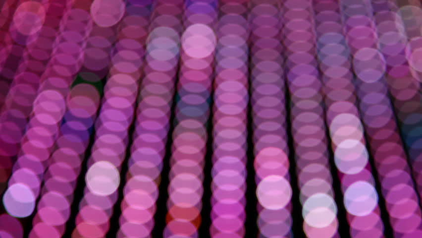 Blurred neon lights, predominantly pink, moving across frame