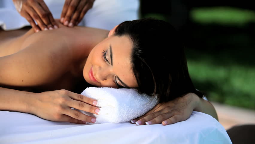 Beautiful young brunette girl relaxing with massage treatment at the health & beauty spa