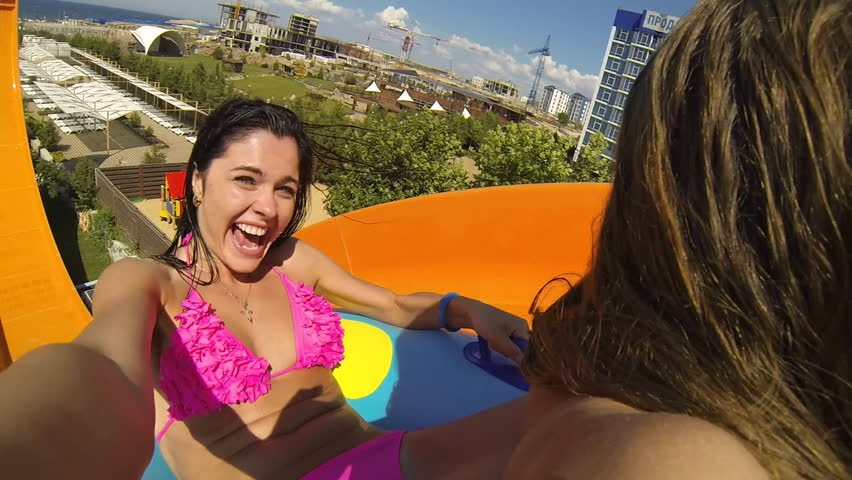 35099bc5e630f Two beautiful young girls ride on the slides at the waterpark and obtain  vivid emotions