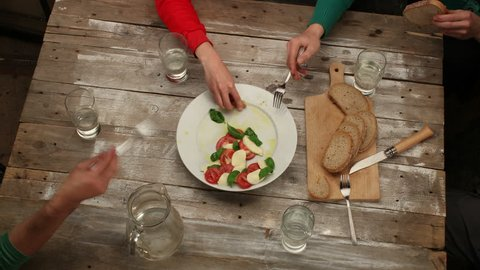 Eating Caprese salad with friends in rustic style - stop motion animation of salad preparation and timelapse of eating, 4K, top view (closeup shot from another angle also available)