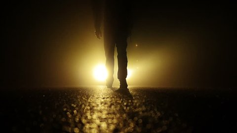low angle view of man feet walking into dark night. mystical fog background. light beams