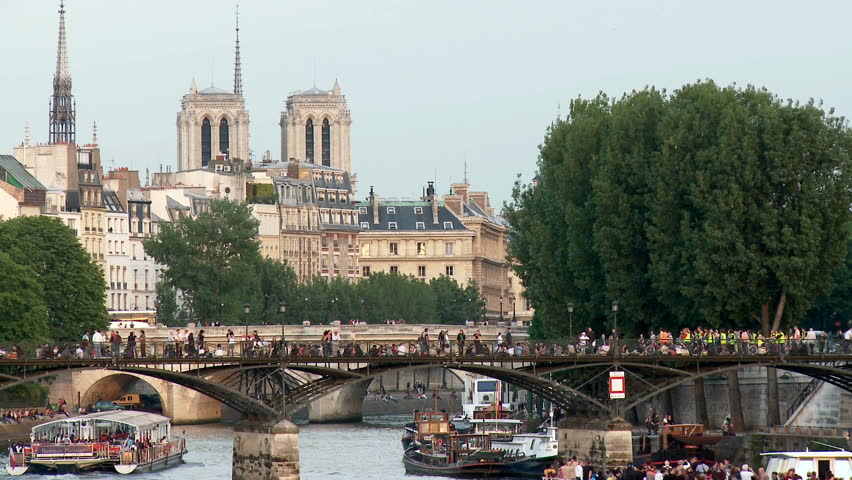 Looking towards the Pont des Arts pedestrian bridge which crosses over the river Seine in Paris France. Notre Dame can be seen in the far distance. | Shutterstock HD Video #7784899