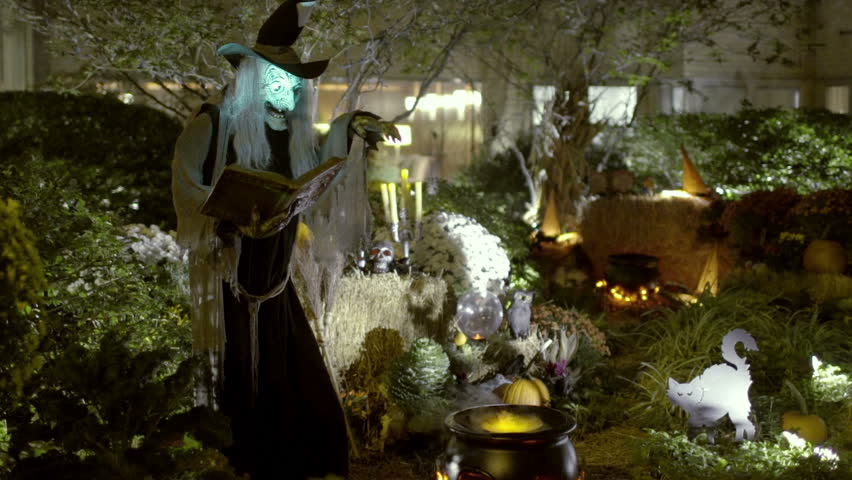 Witch on Halloween - Scary, Spooky Horror Scene at Night with Horrifying Witch Monster Casting Spell over Steaming Smoking Cauldron