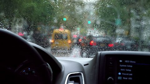 NEW YORK - OCT 23, 2014: driver POV inside car interior, driving in rain in slow motion with windshield wipers in Manhattan New York. 122 days is the average annual precipitation in NYC.