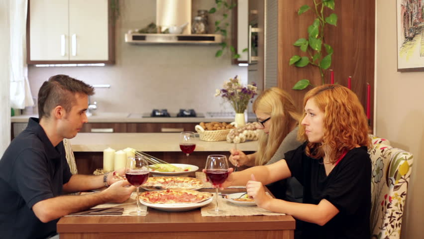Group Of Friends Eating Pizza And Drinking Wine In Dining Room At Home