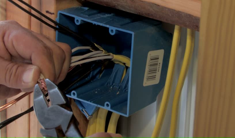 electrician wiring a new wall outlet box in new construction