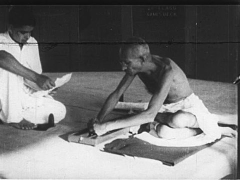 INDIA- CIRCA 1930: Gandhi sits and spins yarn on a loom. Gandhi descends steps, walks through village street, and approaches a home with a young man in a mundu.