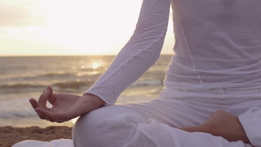 Young beautiful woman is having meditation near the sea: practicing yoga