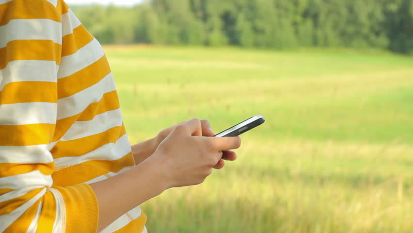 Close-up of girl using smartphone in nature, communicating with people, surfing the internet, camera movement | Shutterstock HD Video #7909516