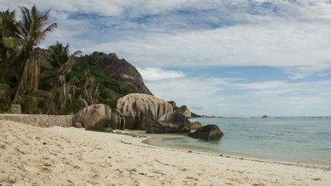 The exotic lagoon at the Seychelles has rocks and trees reaching into the torquoise ocean.