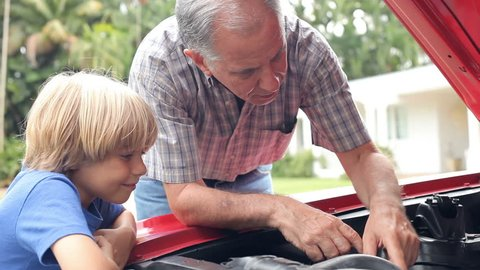 Grandson helping grandfather as he works on engine of restored classic car. Shot on Canon 5D MkII at frame rate of 25fps