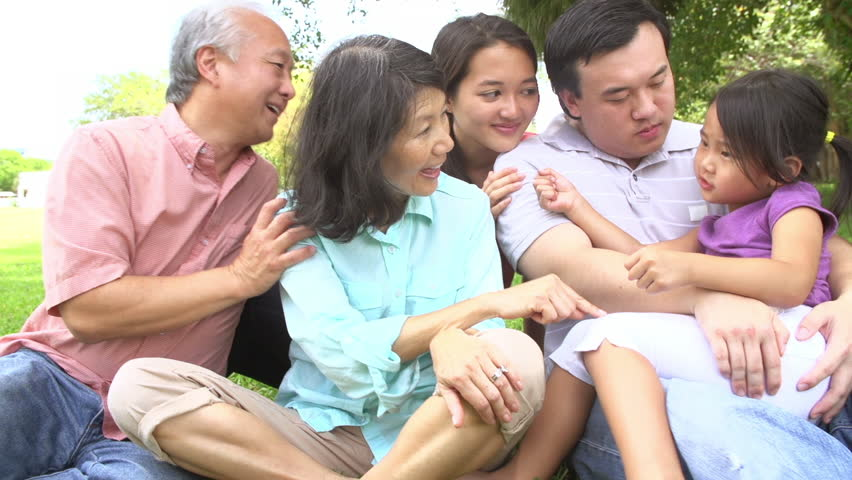 Slow motion sequence of multi-generation Asian family sitting park together - family try to guess which hand object is hidden in. Shot on Sony FS700 at frame rate of 100fps
