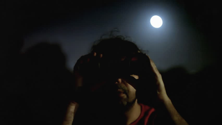 A man is looking through a pair of military binoculars. The night has a pale full moon.  #7926349