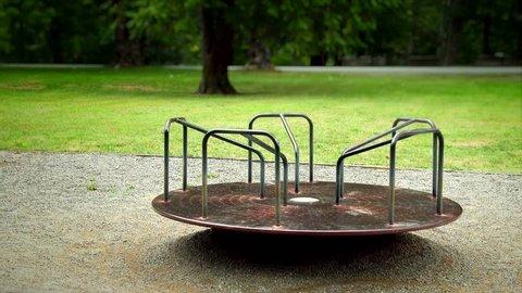 Sad empty merry go round spinning in a playground